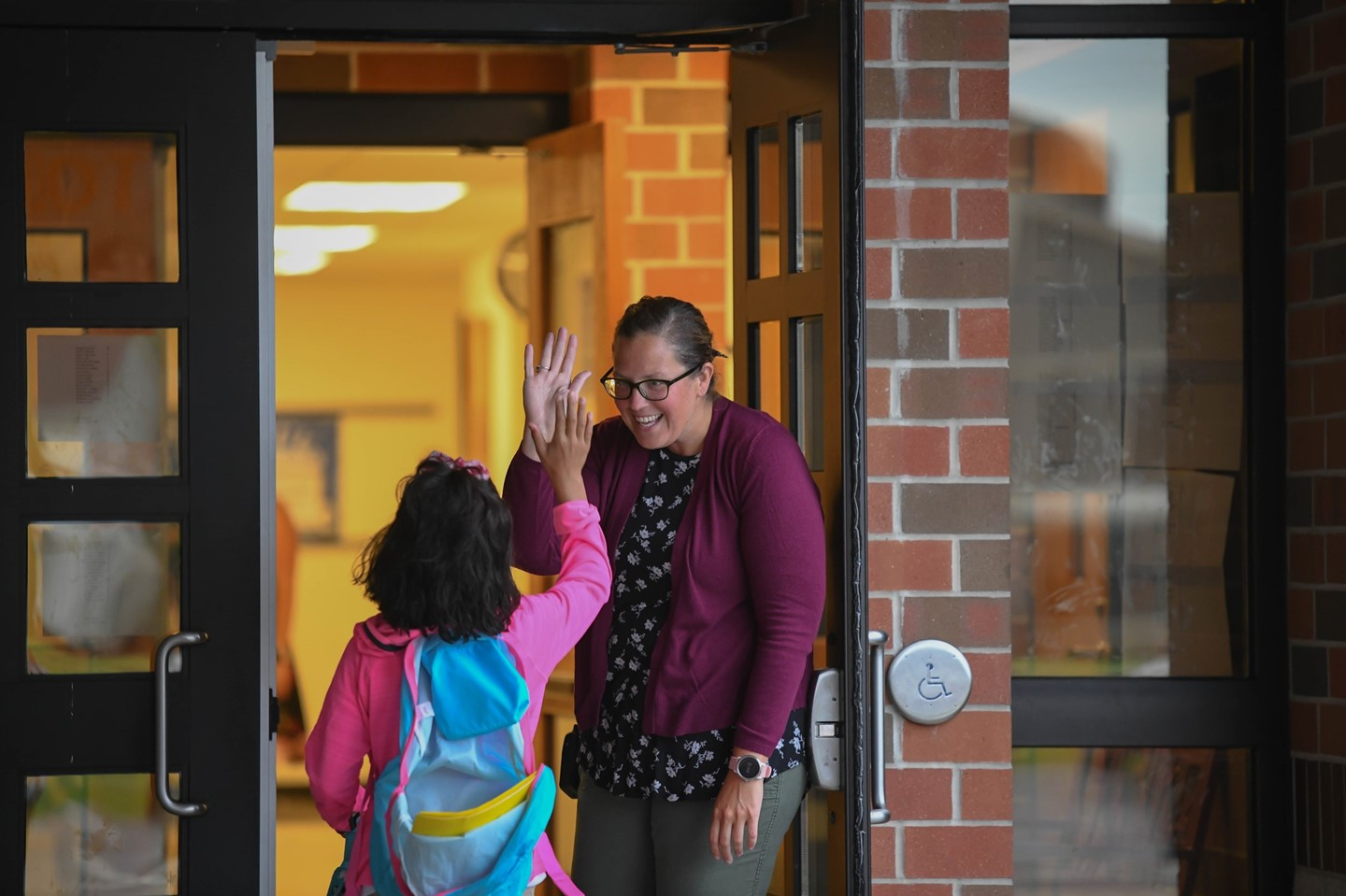 A scholar is high-fived on her way into Admiral King Elementary School