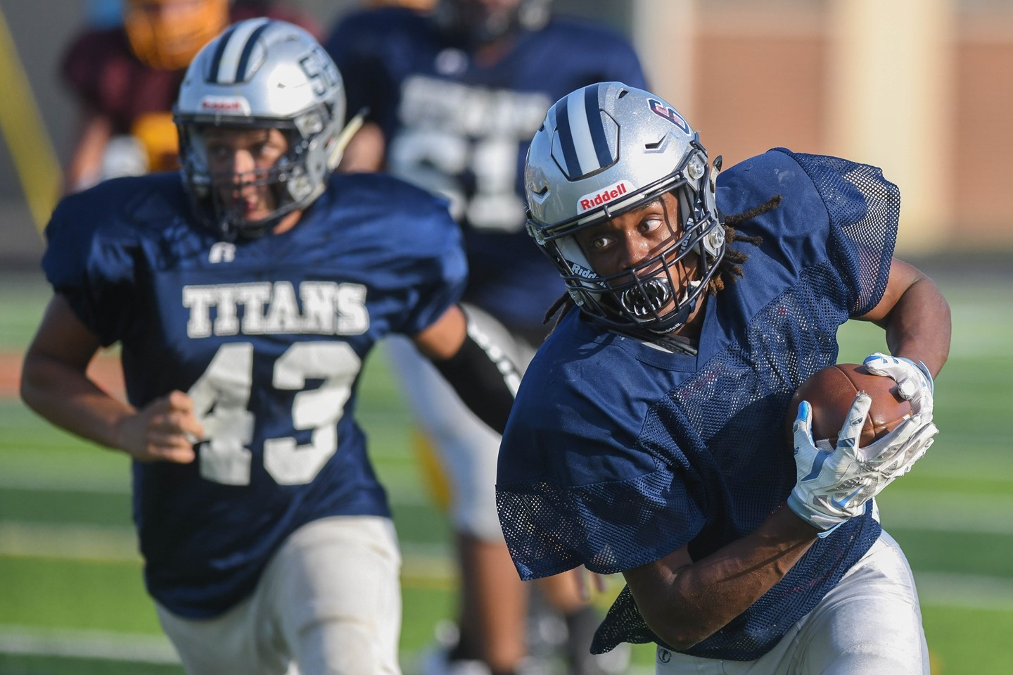 A titans player makes his way into the end zone during a scrimmage football game