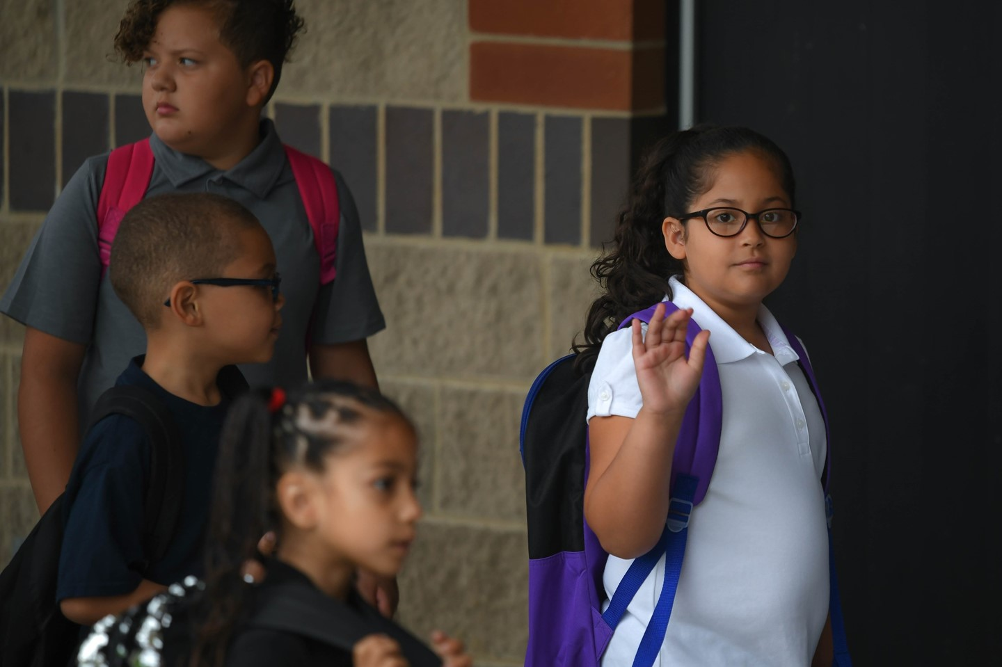 A young scholar waves as she makes her way into the building