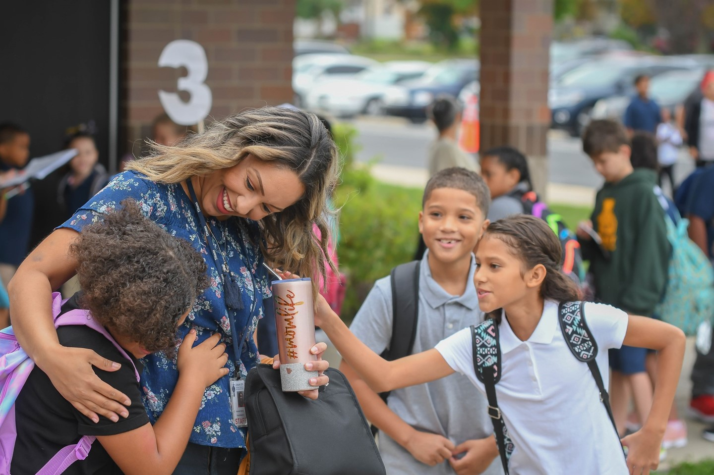 A scholar gets a hug from a teacher on the first day of school