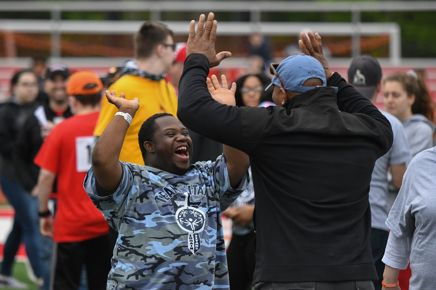 A scholar and staff member celebrate during the Special Olympics