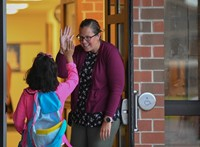 Teacher high fives a student walking in to school