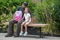 Parent with scholar on the first day of school pose for picture with pink backpack